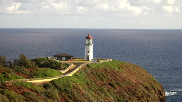 towering light house on large outcropping on kauai island - isola di kauai video stock e b–roll