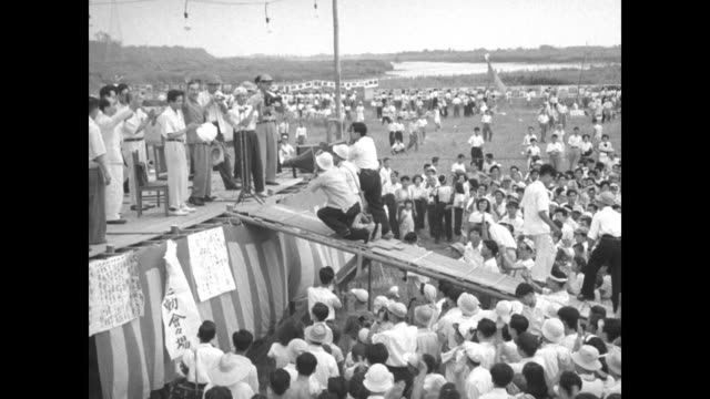 towering scaffolding of bamboo above outdoor stage with banners and flags with pan down to scores of shirtless men waving flags / man in suit... - mao tse tung video stock e b–roll