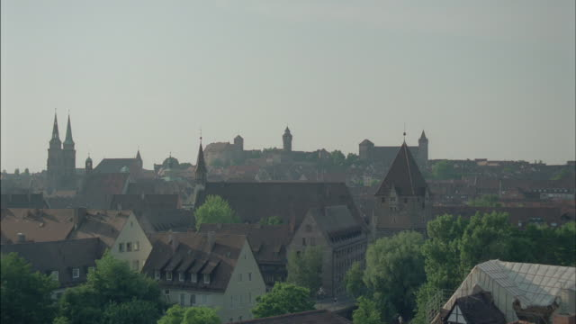 towers and spires rise above rooftops in a german town. - turmspitze stock-videos und b-roll-filmmaterial