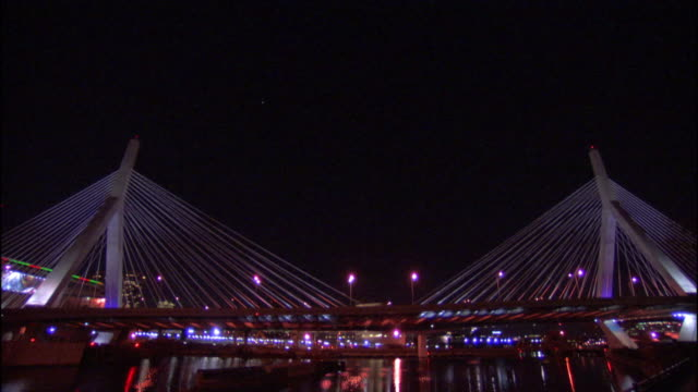towers & cabling of leonard p. zakim bunker hill memorial bridge w/ moving traffic, calm waters of charles river beneath bridge, illuminated... - ザキム・バンカーヒル橋点の映像素材/bロール