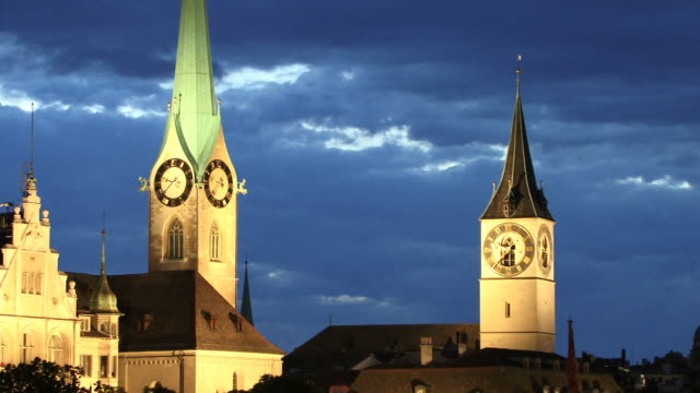 cu, towers of fraumunster and st peter churches illuminated at dusk, zurich, switzerland - altstadt stock-videos und b-roll-filmmaterial