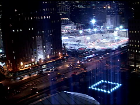 VS Towers of Light tribute near ground zero March 2002 WS tower light projections in FG pit under floodlights in BG traffic at night CU square base...