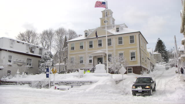 Town hall after snowstorm with traffic and snow-covered roads