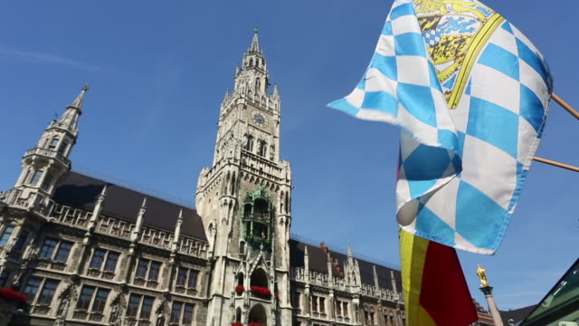 town hall munich with german flagg and bavarian flagg - baviera video stock e b–roll