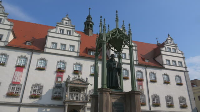 town hall with luther monument on the market square in lutherstadt wittenberg, saxony-anhalt, germany - 宗教的指導者 マルティン・ルター点の映像素材/bロール