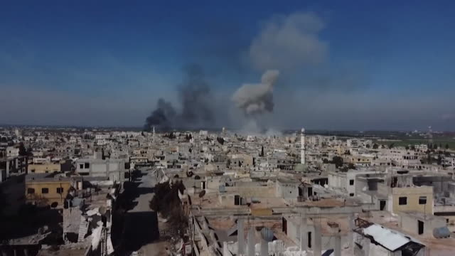 vidéos et rushes de town in idlib that is still a rebel held area, smoke in distance from airstrikes and deserted bomb damaged streets - bombardement