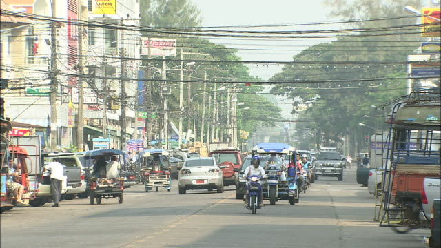 town in nakhon phanom with cars running: long shot. - thailand点の映像素材/bロール