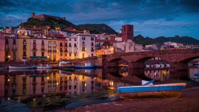 stadt von bosa auf sardinien beleuchtet in der abenddämmerung, italien - sardinien stock-videos und b-roll-filmmaterial