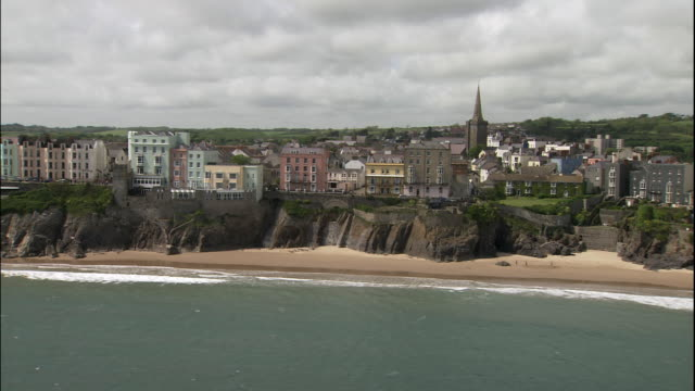 a town perches on cliffs above the ocean near the ruins of st. catherine's fort in tenby, pembrokeshire, wales. - pembrokeshire stock videos & royalty-free footage