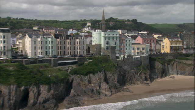 stockvideo's en b-roll-footage met a town perches on the cliffs overlooking the beach in tenby, pembrokeshire, wales. - pembrokeshire