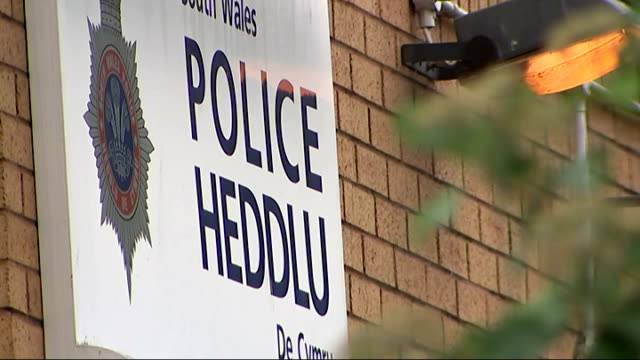 Town seen from above as clouds pass over Tower blocks seen from above View from wing mirror of car as along Reporter to camera 'Heddlu Police' sign...