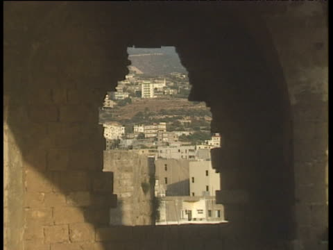 town seen through wall of ruin zoom out to show interior of ruin lebanon - old ruin stock videos & royalty-free footage