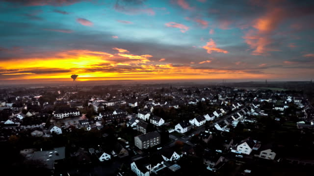 AERIAL : Town under moody sunset clouds