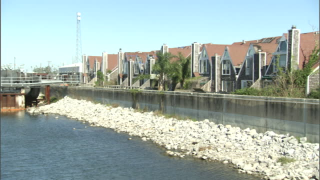 townhouses face a levee and a river in new orleans. - gulf coast states stock videos & royalty-free footage