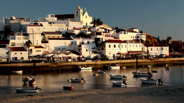 WS Townscape at sunset, fishing boats moored in harbor in foreground / Ferragudo, Algarve, Portugal