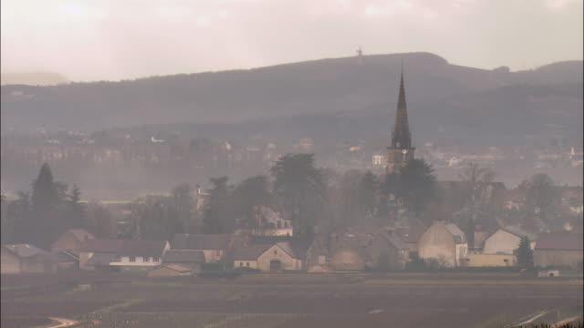 ws townscape through fog / burgundy, france - tornspira bildbanksvideor och videomaterial från bakom kulisserna