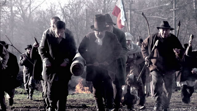 vidéos et rushes de townspeople push a battering-ram across a battlefield during a reenactment of the storming of the bastille. - révolution française