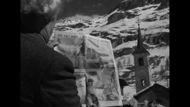 townspeople talking amid wintery scene with snow-covered buildings / an old man reading a newspaper with the steeple of a church beyond / vs people... - steeple stock videos & royalty-free footage