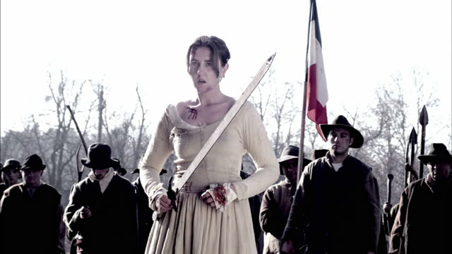 vidéos et rushes de townspeople with weapons wait for orders from a woman during a storming of the bastille reenactment. - révolution française