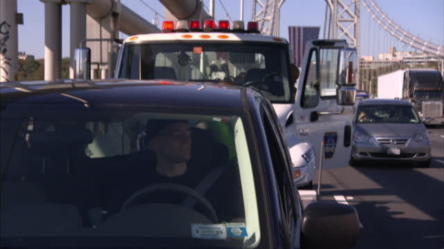 a tow-truck driver speaks to a motorist in his car on a busy freeway. - tow truck driver stock videos and b-roll footage