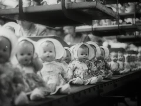 stockvideo's en b-roll-footage met toy dolls move along a conveyer belt in a factory. - pop speelgoed