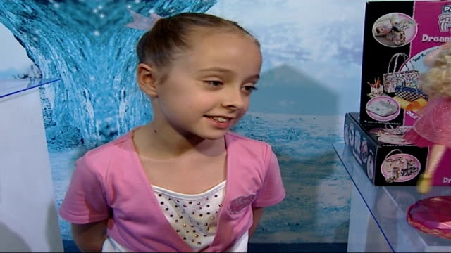 INT Young girl performs ballet moves alongside 'Let's Dance Barbie Doll' performing similar moves watched by reporter Jadie interview SOT ballerina...