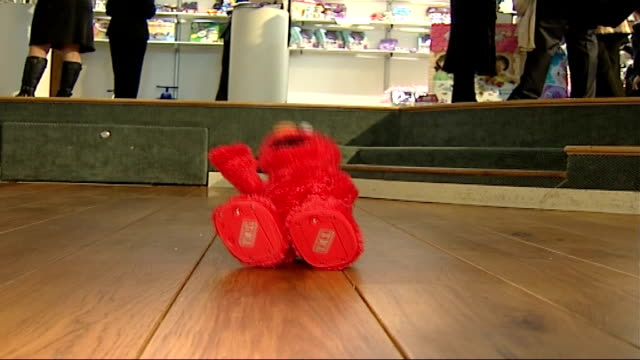 general views of toys on display; red 'elmo' toy waving and lying down in a laughing fit sot / games displayed under sign 'top 12 games' zoom in... - television game show stock videos & royalty-free footage