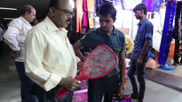 stockvideo's en b-roll-footage met a toy figure dances as commuters walk past during the morning rush hour in mumbai india on thursday feb 26 a vendor sells a electric insect racket... - for sale korte frase