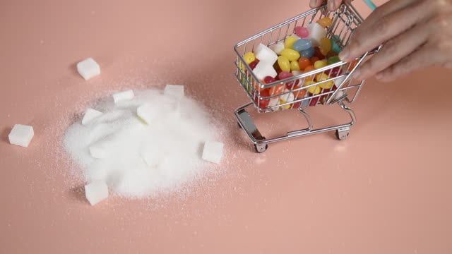 toy shopping trolley dumping sweets on sugar pile - confectionery stock videos & royalty-free footage