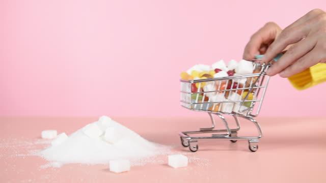 vidéos et rushes de toy shopping trolley dumping sweets on sugar pile - un seul objet