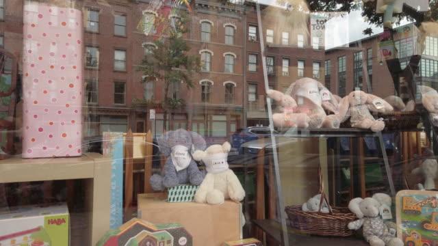 toy store with cute stuffed animals wearing protective face masks. - negozio di giocattoli video stock e b–roll