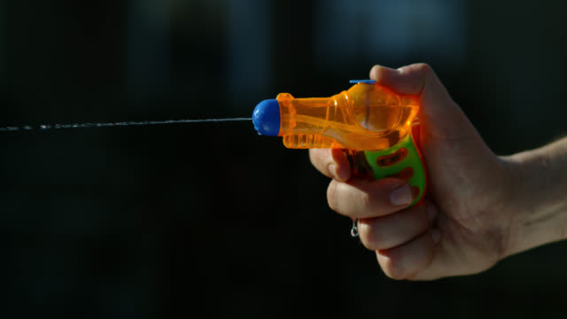 slo mo toy water pistol squirting - focus on foreground stock videos & royalty-free footage