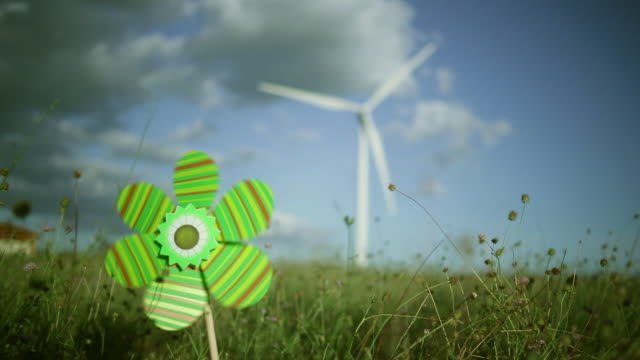 vídeos de stock e filmes b-roll de toy windmill spinning in front of a spinning wind turbine / toulouse, midi-pyrenees, france' - moinho de papel