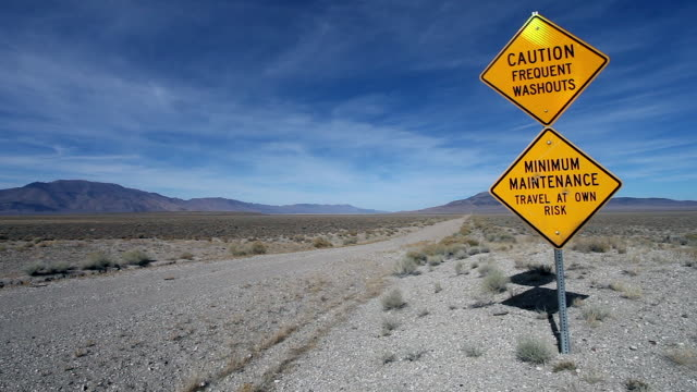 POV of Toyota 4Runner SUV driving away from camera on barren gravel single lane dirt road and caution sign warning of washouts and dangerous conditions through vast flat wide desert landscape and dramatic sky.