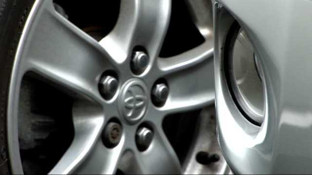 stockvideo's en b-roll-footage met toyota logo on front of car logo on rear of toyota car as driven along road - toyota motor