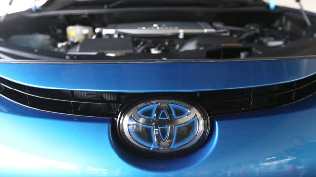 stockvideo's en b-roll-footage met a toyota motor corp mirai fuel cell powered vehicle stands on display above a pool of water at the vehicle's launch event in tokyo japan on tuesday... - toyota motor