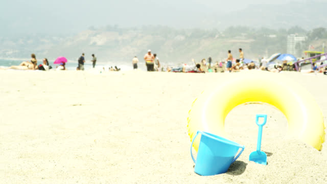Toys on a beach, people in the background