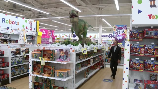 Brent Cross INT Large giraffe model in Toys R Us store Large dinosaur model on display in Toys R Us/ Reporter to camera/