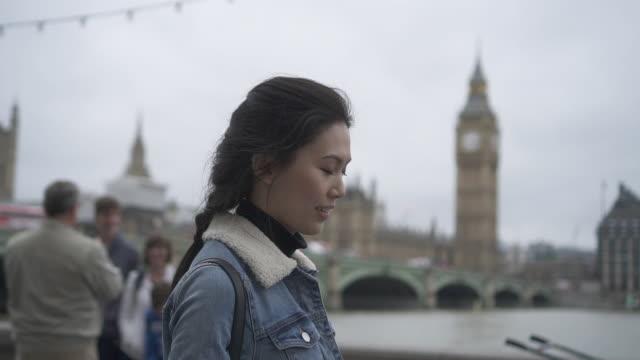 tracing shot, woman walks past big ben in london - big ben stock videos & royalty-free footage