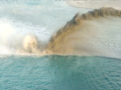 Track above blue sea as sand dredger sprays sediment creating man made island Dubai
