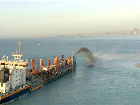 Track above blue sea as sand dredger sprays sediment to create man made island Dubai