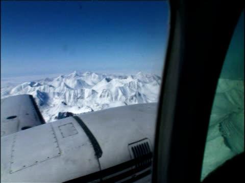 track above frozen landscape as seen from cockpit of aeroplane alaska - 空気力学点の映像素材/bロール