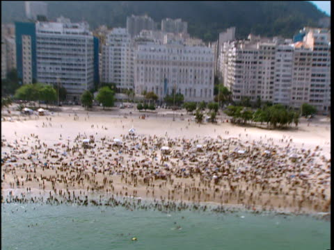 track across copacabana beach crowded with sunbathers high rise hotels and mountains in background - copacabana beach stock videos & royalty-free footage