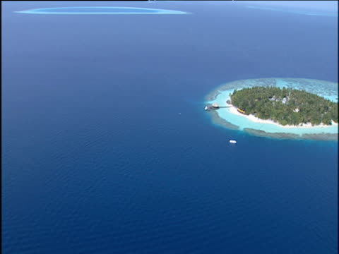 Track across dark blue sea to lush tropical Island of Male surrounded by turquoise waters and coral reefs Maldives