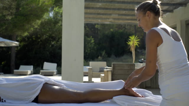 track across mature female client receiving a massage - masseur stock videos & royalty-free footage