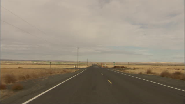 track along a highway stretching out through the desert available in hd. - shrubland stock videos & royalty-free footage