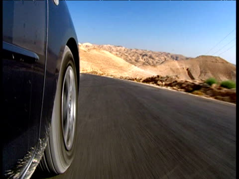vidéos et rushes de track along barren road at speed by wheel of car west bank israel - macadam
