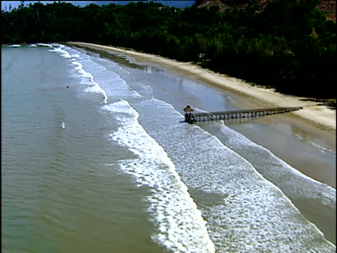Track along empty tree lined beach past small wooden pier waves breaking on beach Borneo
