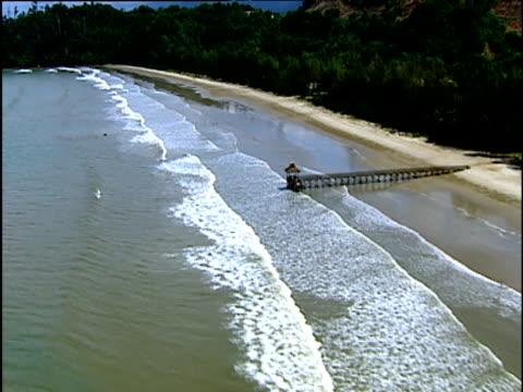 track along empty tree lined beach past small wooden pier waves breaking on beach borneo - ボルネオ島点の映像素材/bロール