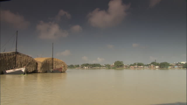 track along hooghly river past huge bales of straw on barges, kolkata available in hd. - hooghly river stock videos & royalty-free footage